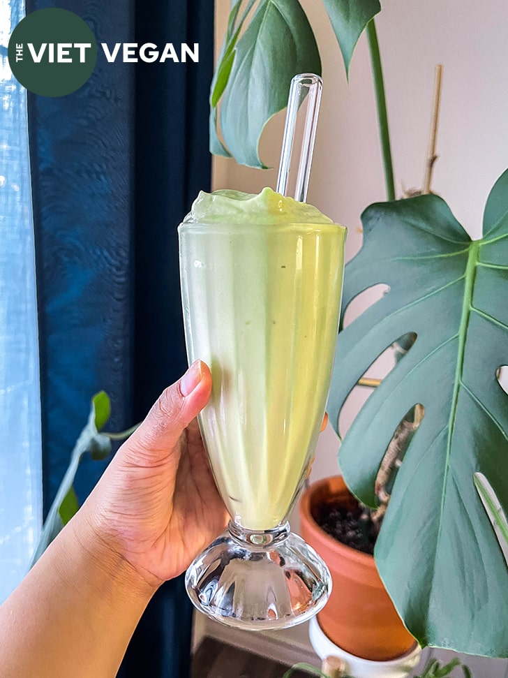 avocado smoothie in a milkshake glass with a glass straw, held in front of some houseplants