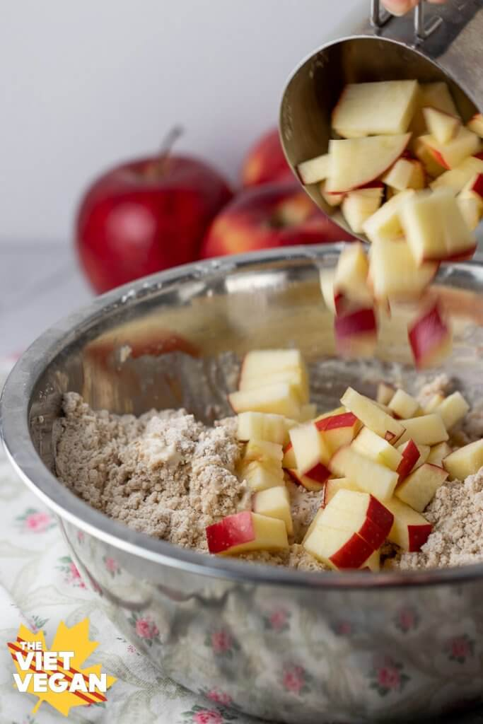 Apples falling from a measuring cup onto batter