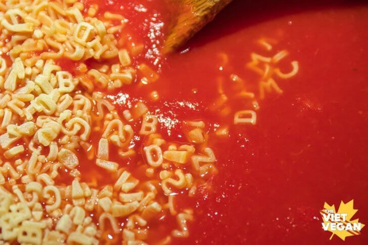 alphabet pasta in a pot about to be mixed into tomato soup