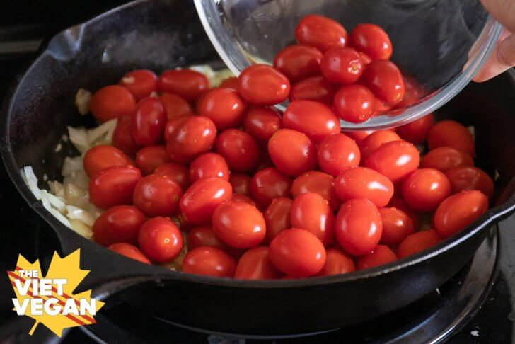 pouring cherry tomatoes into a cast iron skillet
