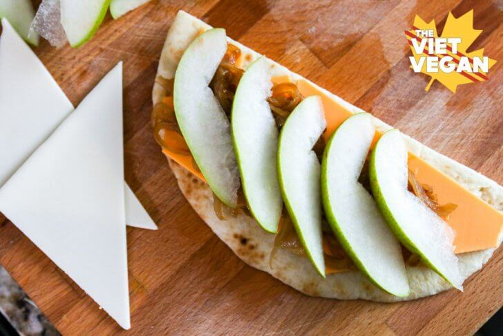 A top view of sliced pear layered on top of caramelized onions, vegan cheese, and half moon of naan bread on a cutting board