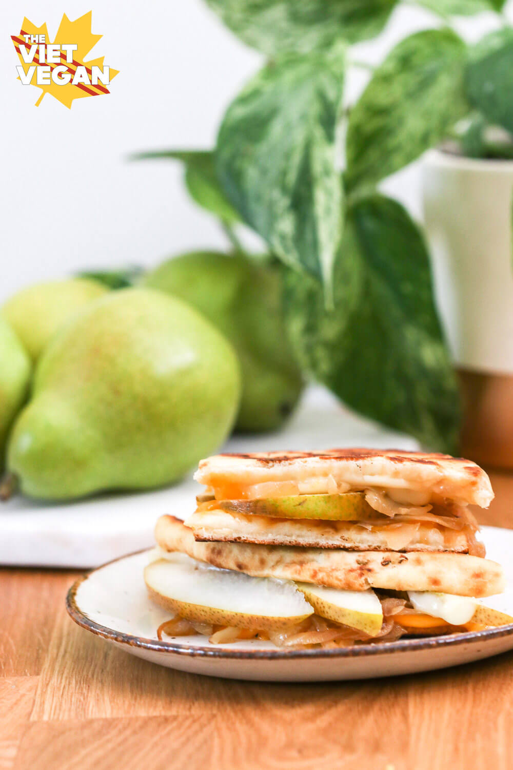Vegan grilled cheese sandwich with pears and a plant in the background