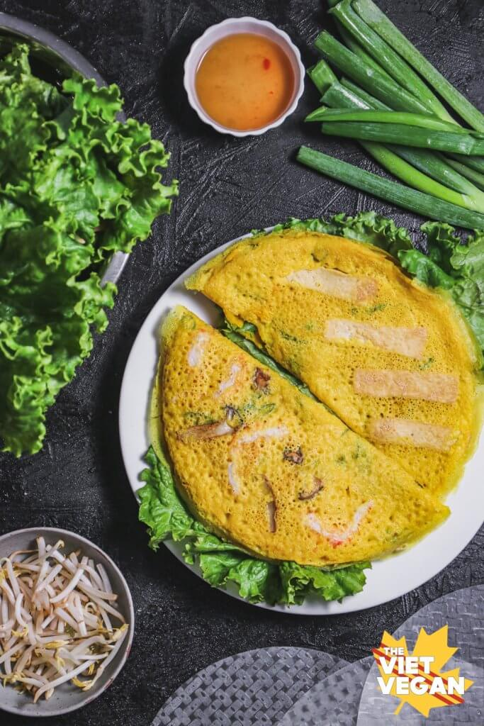 Vegan banh xeo aka Vietnamese pancake on a dish, surrounded by ingredients