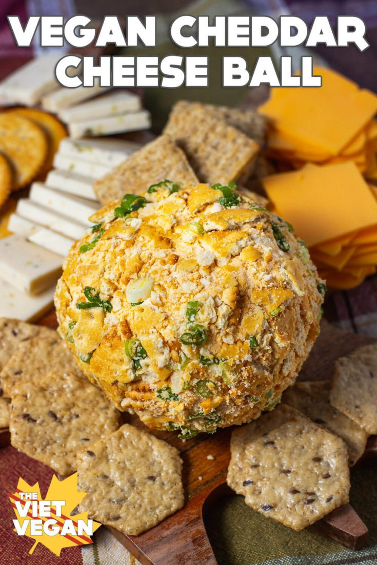 Vegan Cheddar Cheese Ball on a cheese board surrounded by vegan cheese & crackers