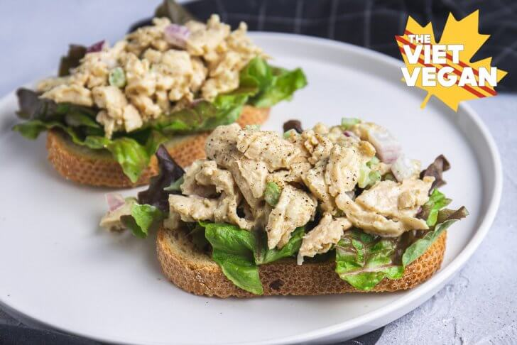 Two vegan chicken salad open faced sandwiches, on a plate with a napkin close up