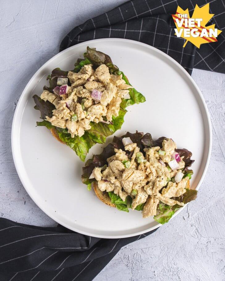 Two vegan chicken salad open faced sandwiches, on a plate with a napkin shot from above