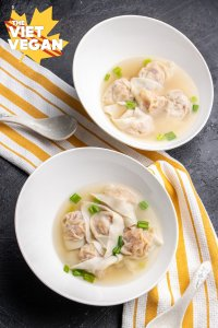 vegan wonton soup in bowls, on a yellow and white kitchen towel, with a spoon, vertical