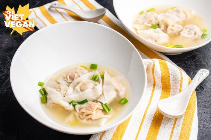 vegan wonton soup in bowls, on a yellow and white kitchen towel, with a spoon