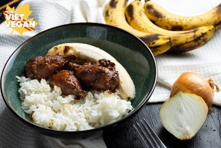 vegan adobo drumsticks in a bowl with rice and a banana, a sliced onion and whole bananas around for decoration