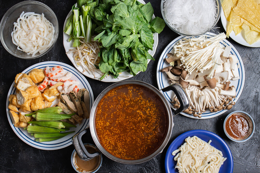 ingredients to put in hot pot on plates surrounding a pot of broth