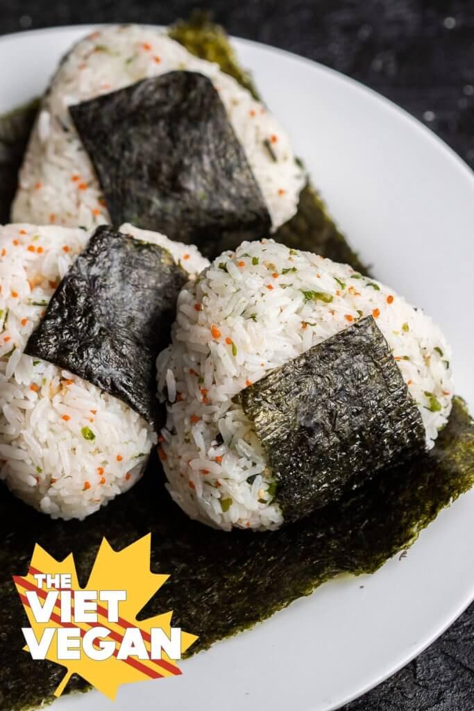 three onigiri on a sheet of nori on a plate