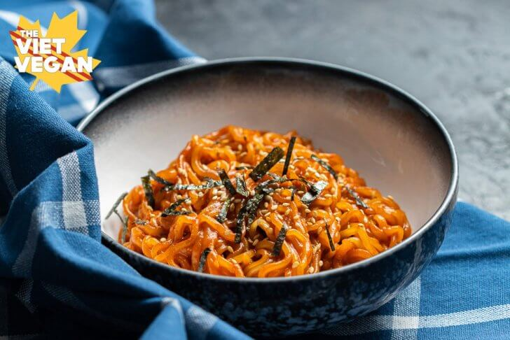 red ramen noodles topped with sesame and nori in a bowl, set on a blue kitchen cloth on a black surface, from the front