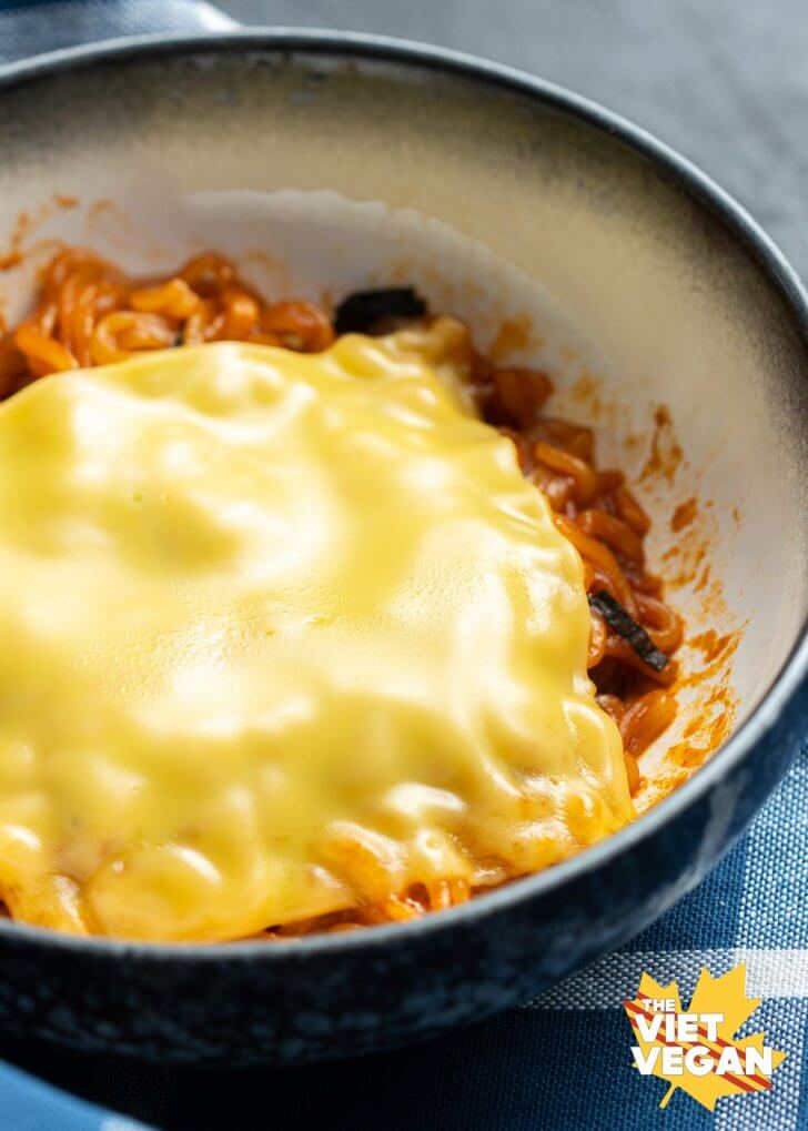 red fire noodles in a bowl topped with a slice of melted american-style cheese