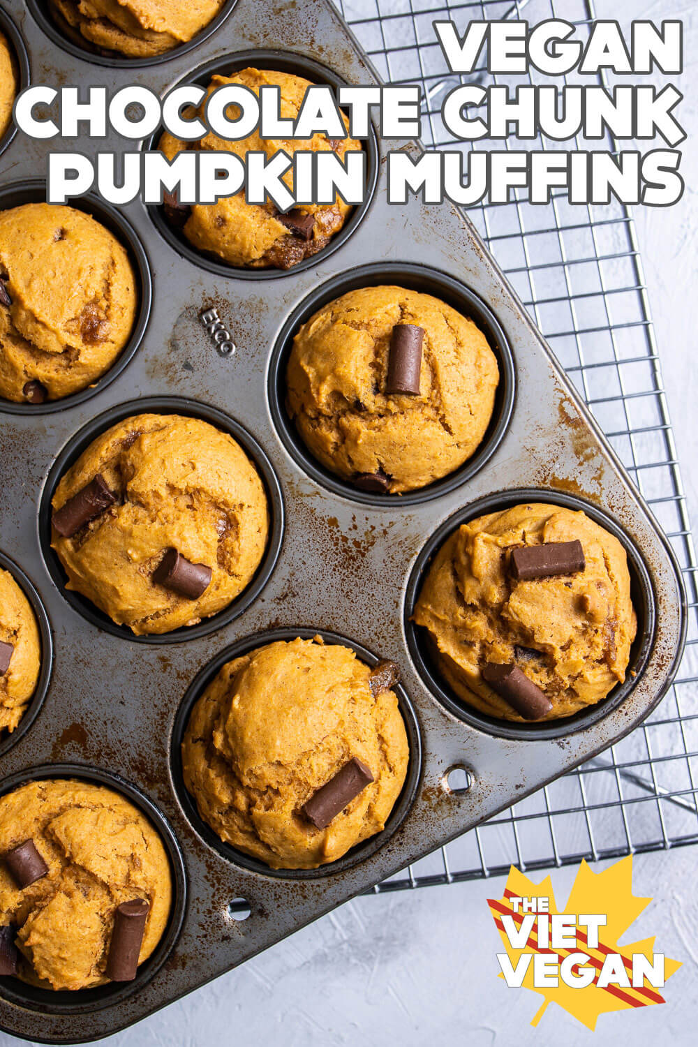 baked muffins in a baking pan on a cooling rack, on a white surface