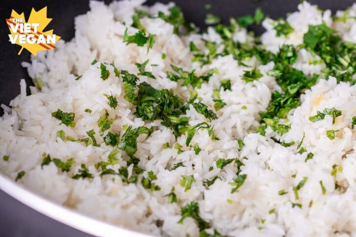 cooked rice in a pan with cilantro on top before mixing in