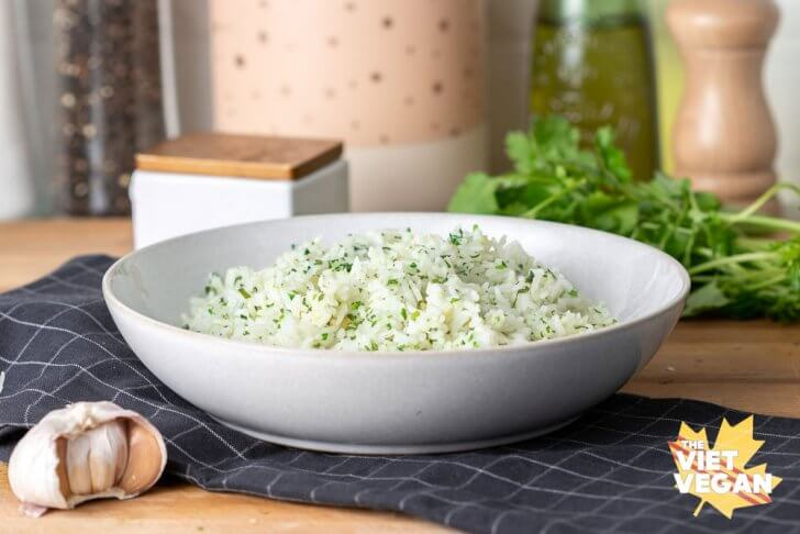 finished cilantro rice in a bowl on a tea towel with cilantro and garlic