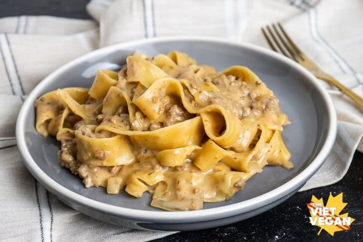 a serving of the finished pasta on a grey plate, on top of a beige plaid tea towel