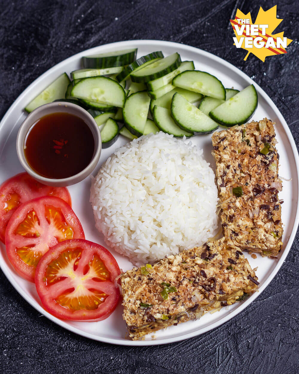 meatloaf slices on a plate with a mound of white rice, cucumber, sliced tomato, and sauce, from above