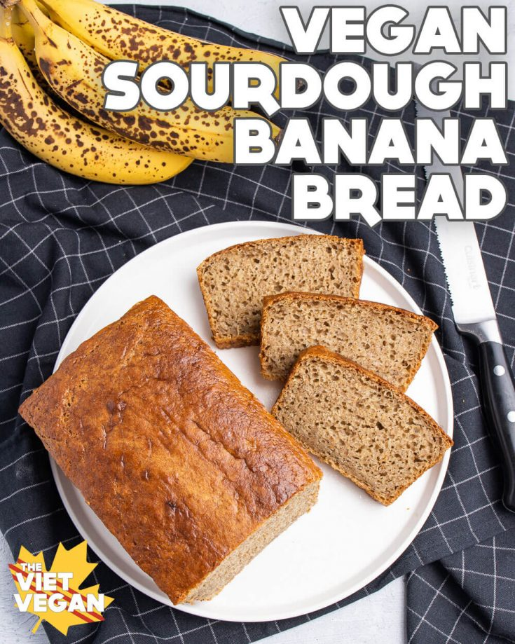 vegan sourdough banana bread, sliced and displayed on a white plate, on a black grid-patterned tea towel, with overripe bananas and a bread knife