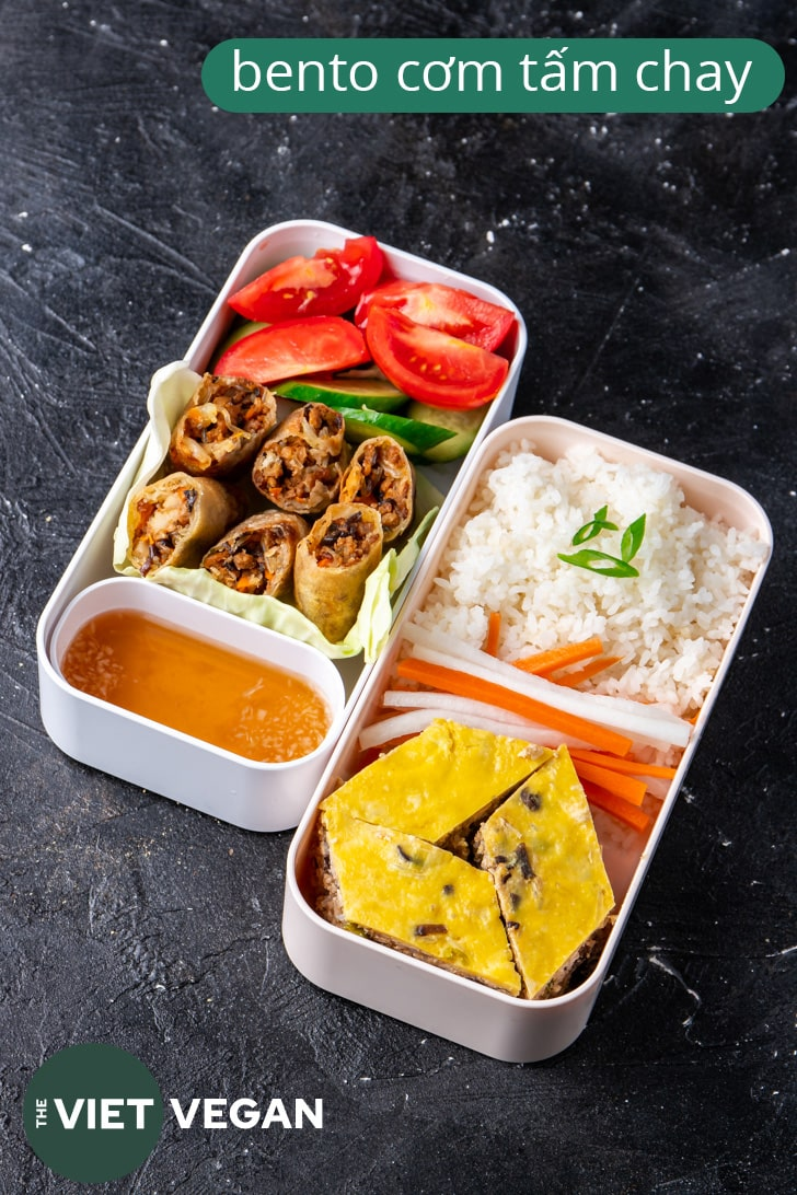 Vietnamese bento with two layers, one with rice, egg meatloaf, pickled carrots and daikon, the other with spring rolls and vegetables and sauce