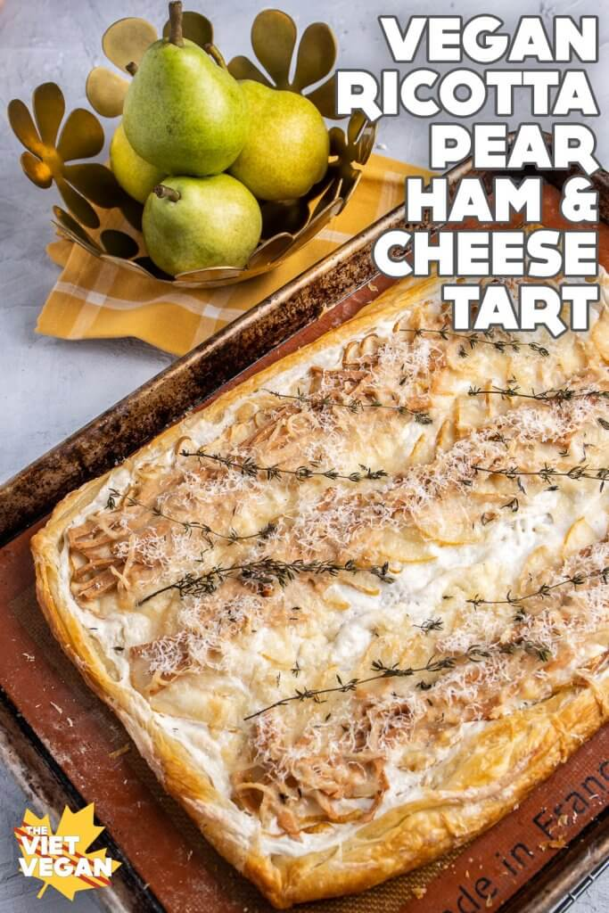 Baked pear, ham and cheese tart on the tray, with a fruit bowl of California pears