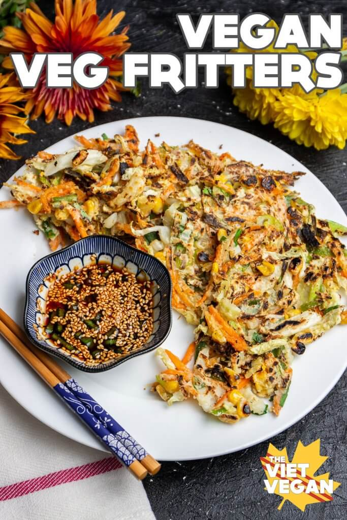Text overlay on a photo of Vegan vegetable fritters on a plate with dipping sauce, surrounded by autumn flowers (dahlias)