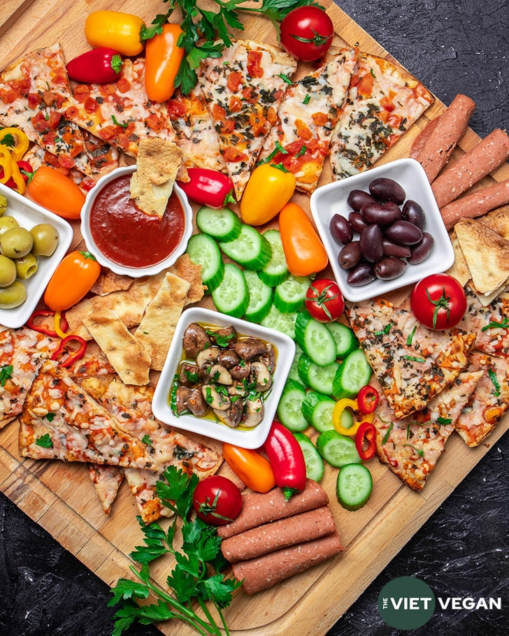 Overhead shot of snack board, three bowls contain black olives, green olives, sauce, and marinated mushrooms, and are surrounded by baked Wholly Veggie Pizza and sliced fresh veggies