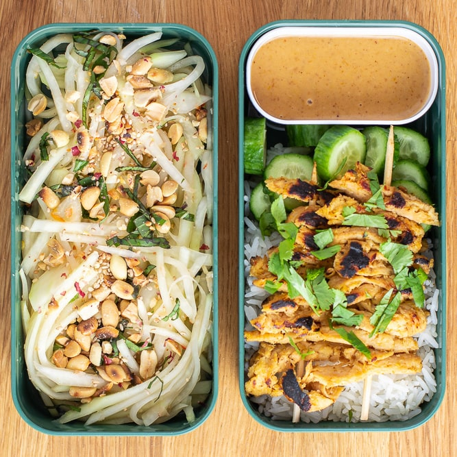 Two rectangular bento containers with green papaya salad in the left, and rice, peanut sauce, cucumbers, and satay soy curl skewers on the right