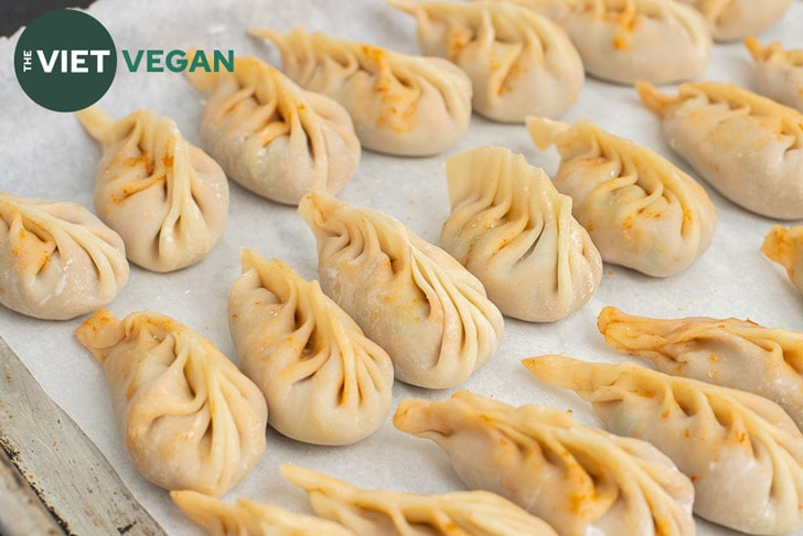 a dozen or so braided dumplings, uncooked, on a parchment paper lined baking sheet