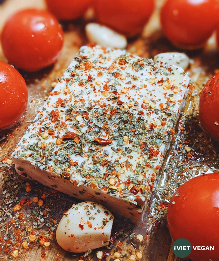 feta in a casserole dish, surrounded by tomatoes and garlic, sprinkled with herbs and spices and olive oil