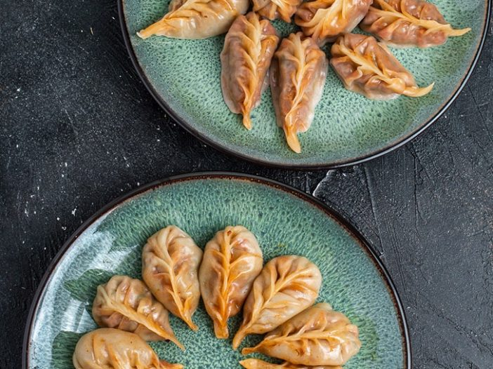 two plates of red curry braided dumplings, one is steamed, one is steam fried