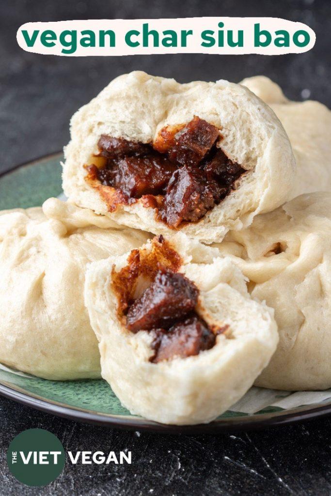 A plate of vegan char siu bao buns with one split open to reveal the char siu seitan inside