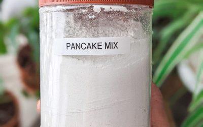 """dry vegan pancake mix in a tub with """"pancake mix"""" label on it"""