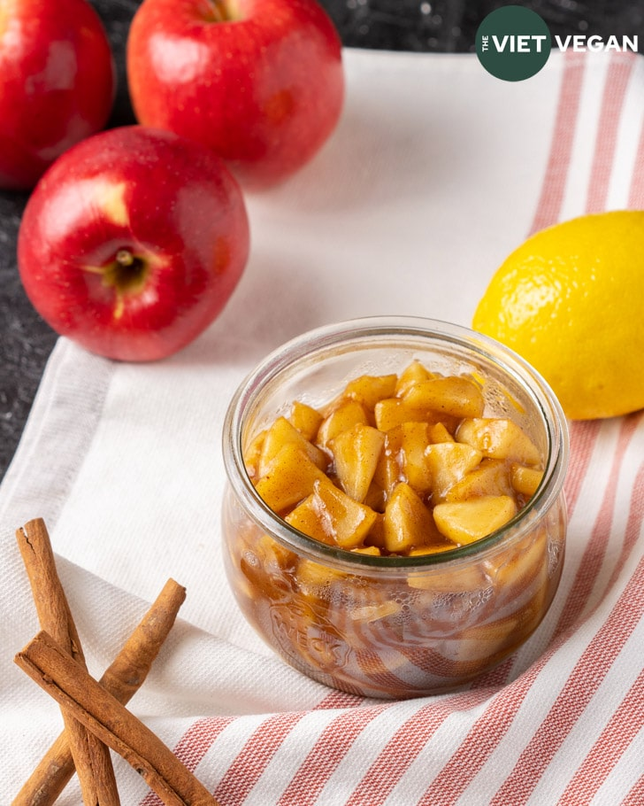 apple pie filling in jar surrounded by apples, lemon, and cinnamon