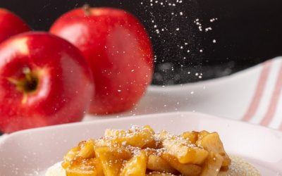 apple pie pancakes with apples in background and dusting of icing sugar