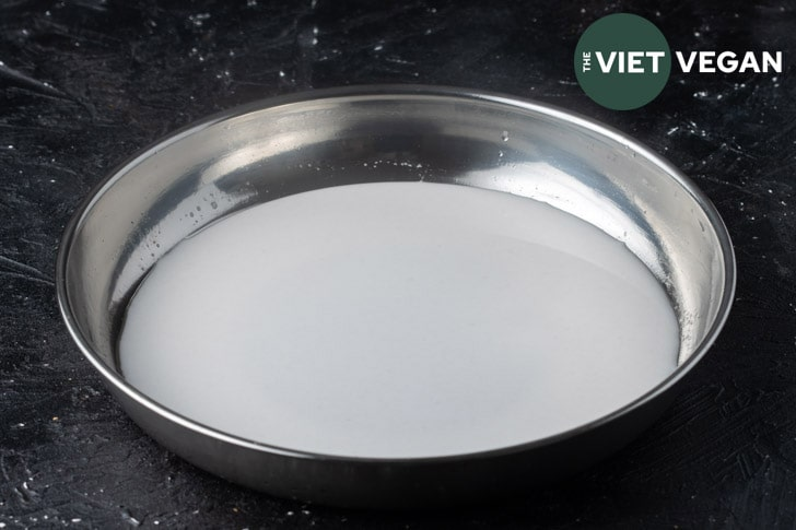 wheat starch noodle batter in a stainless steel non-stick pan to be steamed