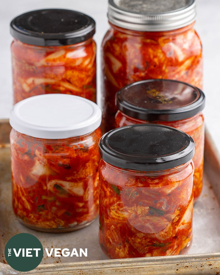 5 jars of kimchi fermenting on a baking tray