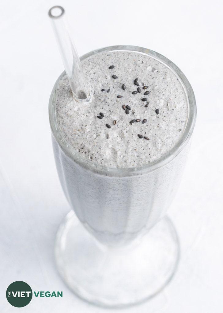 black sesame milkshake in large milkshake glass with a glass straw, garnished with black sesame seeds