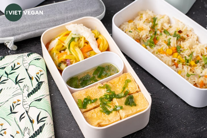 fried tofu with sauce in a bento box with green mango salad, fried rice on the side