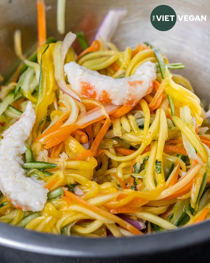 Green mango salad tossed with a vegan fish sauce mixture and topped with vegan shrimp
