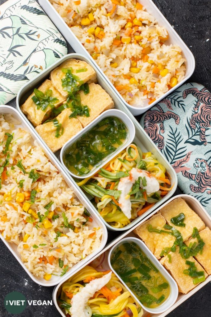 Bento Box from above with fried tofu, sauce, green mango salad, and fried rice layers