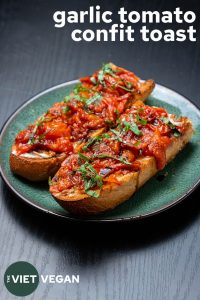 two pieces of toast with garlic tomato confit and text in the corner
