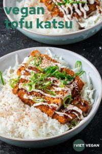 Vegan Tofu Katsu in a bowl drizzled with tonkatsu sauce, vegan mayo, scallions, sesame seeds, on a bed of shredded cabbage and rice