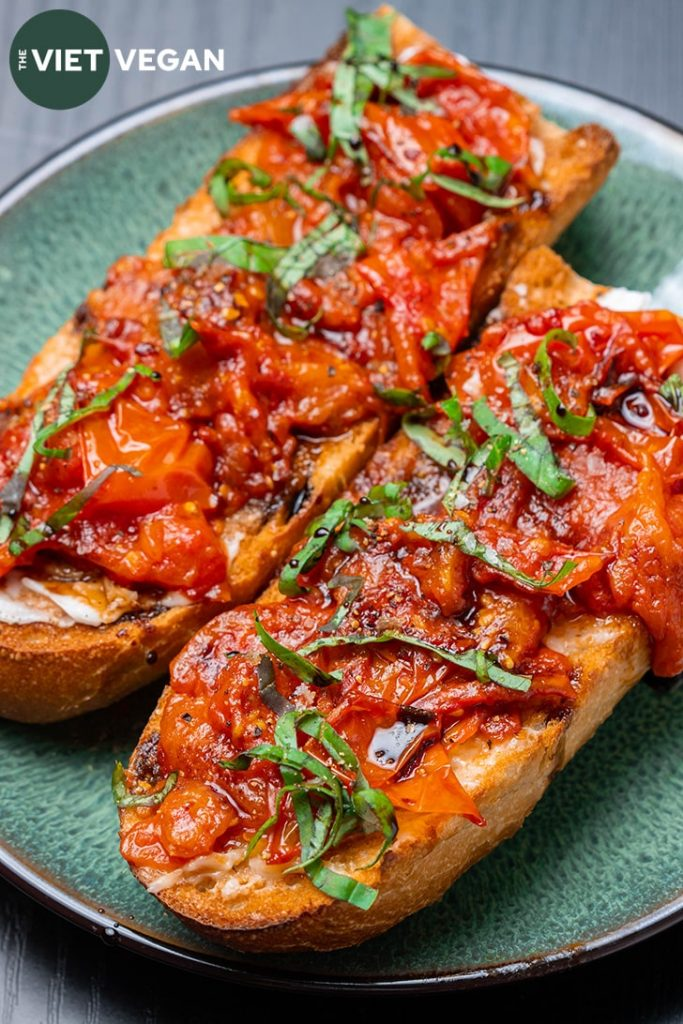 toast close up with garlic tomato confit on a green plate