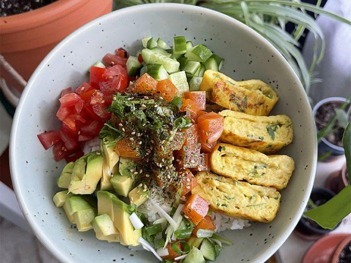 Vegan poke bowl filled with tomatoes, avocado, vegan salmon poke, cucumber, and vegan tamagoyaki over a bed of rice