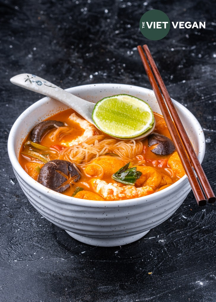 A side angle of tom yum noodle soup in a large soup bowl on a dark, uneven textured background