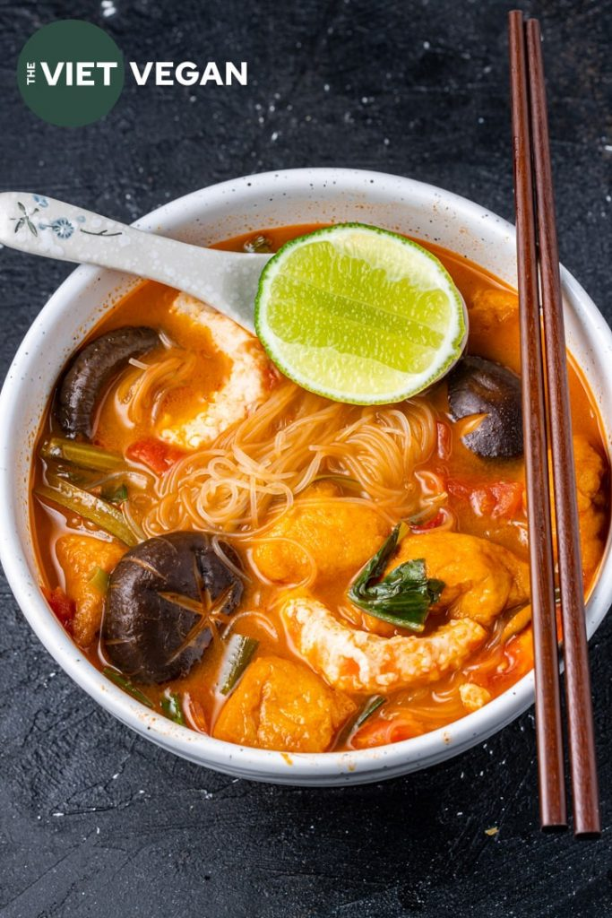overhead photo of tom yum noodle soup with lime, mushrooms, vegan shrimp, noodles, tomatoes, and wooden chopsticks on the edge of the bowl